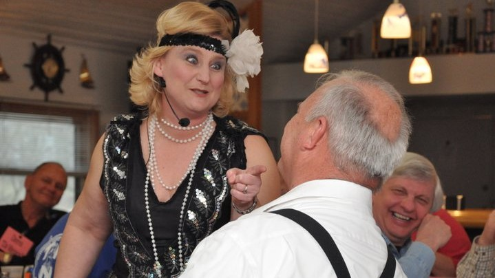 1920's flapper interrogates mobster at murder mystery Christmas party